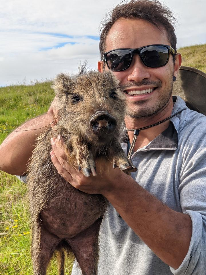 picture of Michael Peyton posing with one of Kohala's numerous feral piglets